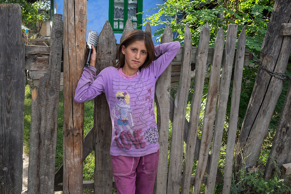 A Roma girl with a hairbrush in her hand leans against a fence in the all-Roma village of Poiana Negustiorului in Bacau County, Romania.