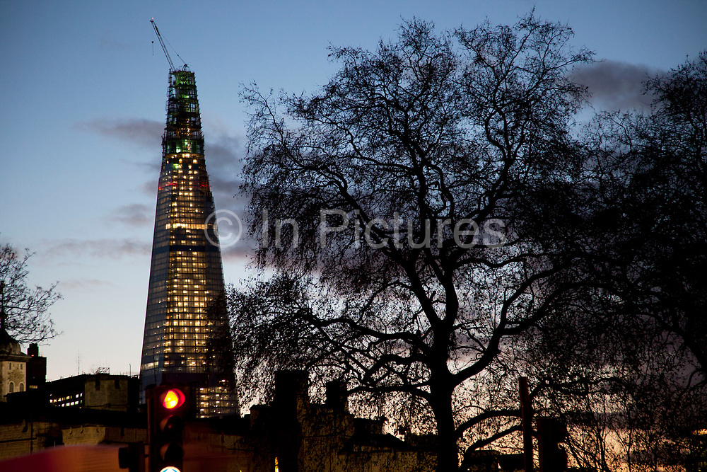 The Shard, under construction at night sits behind the silhouette of a giant tree. The Shard (aka The Shard of Glass) is being built on the south side of the city near London Bridge. Shard London Bridge, previously known as London Bridge Tower, and also known as the Shard of Glass. The Shard is a supertall skyscraper under construction in Southwark. When completed in 2012 it will be the tallest building in the European Union. The tower will stand at 310 m (1,017 ft) tall and have 72 floors, plus 15 further floors in the roof. Renzo Piano, the building's architect, worked together with architectural firm Broadway Malyan during the planning stage of the project. After a lengthy public inquiry, the collaboration successfully achieved its objective, and the developers were granted full planning permission in November.