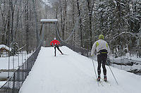 Cross-country skiers on Suspension Bridge over Metho River in winter, North Cascades Washington