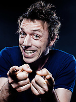 studio portrait on black background of a funny expressive caucasian man pointing happy friendly