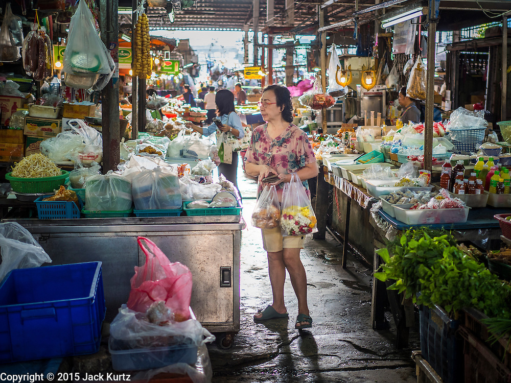 29 JUNE 2015 - BANGKOK, THAILAND:  A woman walks through the Bang Chak Market in Bangkok. The Bang Chak Market serves the community around Sois 91-97 on Sukhumvit Road in the Bangkok suburbs. About half of the market has been torn down, vendors in the remaining part of the market said they expect to be evicted by the end of the year. The old market, and many of the small working class shophouses and apartments near the market are being being torn down. People who live in the area said condominiums are being built on the land.    PHOTO BY JACK KURTZ
