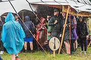 A short burst of heavy rain makes some people seek cover, others put their wellies and ponchos to good use. The 2015 Glastonbury Festival, Worthy Farm, Glastonbury.