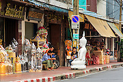 """12 NOVEMBER 2012 - BANGKOK, THAILAND:   Men set on Bamrung Muang Street in Bangkok. Thanon Bamrung Muang (Thanon is Thai for Road or Street) is Bangkok's """"Street of Many Buddhas."""" Like many ancient cities, Bangkok was once a city of artisan's neighborhoods and Bamrung Muang Road, near Bangkok's present day city hall, was once the street where all the country's Buddha statues were made. Now they made in factories on the edge of Bangkok, but Bamrung Muang Road is still where the statues are sold. Once an elephant trail, it was one of the first streets paved in Bangkok. It is the largest center of Buddhist supplies in Thailand. Not just statues but also monk's robes, candles, alms bowls, and pre-configured alms baskets are for sale along both sides of the street.    PHOTO BY JACK KURTZ"""