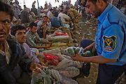 A policeman examines a bag of at qat before buying from a vendor at the qat market in souk of BinAifan, Wadi Do'an, Hadhramawt, Yemen.