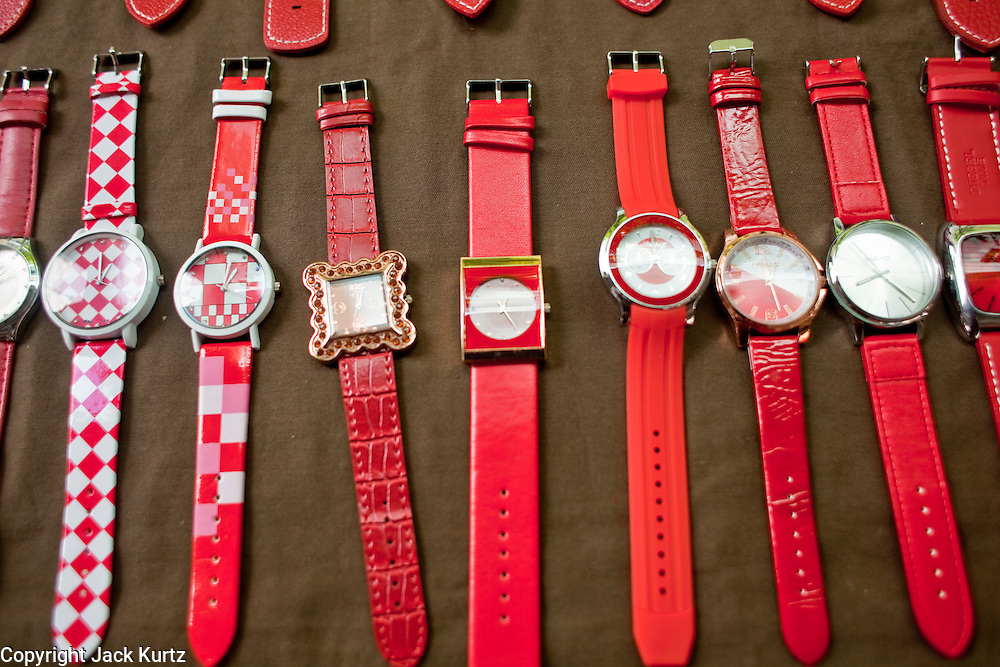 18 APRIL 2010 -- BANGKOK, THAILAND: Watches with a Red theme for sale on the street near the protest area. The Red Shirts protest in the Ratchaprasong Shopping district, home to Bangkok's most upscale malls, is costing the Thai economy millions of Baht per day because the malls and most of the restaurants are closed and tourists are staying away from the area. But that hasn't stopped the Red Shirts who have brought their own economy with them. There are Red Shirt restaurants, food stands, souvenir vendors and more, creating a micro economy for Red Shirts in the area.  The Red Shirts continue to occupy Ratchaprasong Intersection an the high end shopping district of Bangkok. They are calling for Thai Prime Minister Abhisit Vejjajiva to step down and dissolve the parliament. Most of the Red Shirts support ousted former Prime Minister Thaksin Shinawatra.   PHOTO BY JACK KURTZ