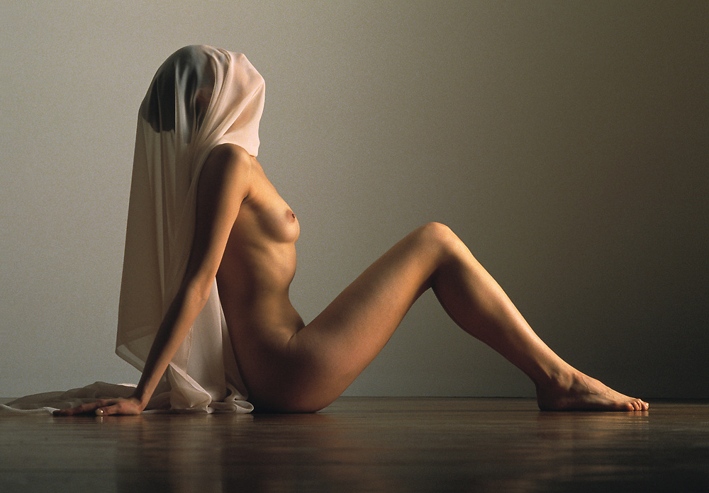 Profile photo of nude woman sitting on wood floor with sheer pink cloth covering face