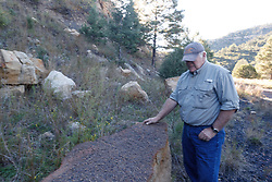 Man examining fossilized slab or stone,  Koehler Coal Mining Town, Vermejo Park Ranch, New Mexico, USA.