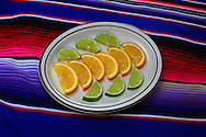 A plate of fruit with lime and oranges.