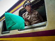 10 JULY 2018 - NAKHON PATHOM, THAILAND:  A conductor waves his train out of the the station in Nakhon Pathom. Nakhon Pathom is about 35 miles west of Bangkok. It is one of the oldest cities in Thailand, archeological evidence suggests there was a settlement on the site of present Nakhon Pathom in the 6th century CE, centuries before the Siamese empires existed. The city is widely considered the first Buddhist community in Thailand and the nearly 400 foot tall Phra Pathom Chedi is considered the first Buddhist temple in Thailand.    PHOTO BY JACK KURTZ