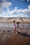 A girl walks by two boys wading in Medano Creek, Great Sand Dunes National Park and Preserve, Colorado.