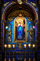 """""""Madonna illuminates the altar of Santa Maria Sopra Minerva, Assisi""""…<br /> <br /> Santa Maria Sopra Minerva is the church dedicated to Mary which was built over a Roman temple to Minerva, the goddess of wisdom. Parts of the Roman temple which dates from the time of Augustus (63 BC-AD 14) remain. As Christianity became official in the Roman Empire, the Temple became abandoned. Benedictine monks restored the temple and eventually, the Italian Renaissance-inspired a newfound appreciation for classical art and architecture. In 1539, Pope Paolo III ordered the Temple of Minerva to be completely restored and dedicated to the Virgin Mary, queen of true wisdom. The temple then took the name of Santa Maria Sopra Minerva. The six imposing Corinthian columns and the entire Roman façade are still intact after 2,000 years along with the towering Campanile. As the center of ancient Assisi, and still prominent today… this former Temple and now sacred church seems to be at the heart of the existence of Assisi. Additionally, the famous artist Giotto painted frescos of the life of Saint Francis which adorn the walls of the Saint's Basilica including images of Santa Maria Sopra Minerva. Ironically, Giotto's placing of St. Francis in the local scenery was the first of its kind, thus the beginning of the Renaissance. In 1791 it was consecrated on the Solemnity of the Assumption of Our Lady. And, after the Apparition of Our Lady as the Immaculate Conception seen by St. Bernadette which took place in Lourdes, France…this statue of the Virgin Mary was erected in the hollowed earth behind the altar. As I hiked the steep grade upward to the top of Assisi, a respite seemed to arise from the ancient Roman era and took me back in time. The imposing columns gave way from the ancient exterior progressing inside discovering the serene and peaceful Virgin Mary, Queen of True Wisdom."""