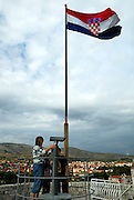 Woman and two children on lookout atop Kamerlengo fortress, township of Trogir in distance, Croatian national flag flying. Trogir, Croatia