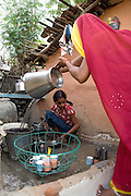 Pooja, 14, a student from the village of Pathpuri, Hoshangabad, Madhya Pradesh, India, taking part to the children's journal, a project launched by Dalit Sangh, an NGO which has been working for the uplift of scheduled castes for the past 22 years, is washing the dishes helped by her mother in their home. Dalit Sangh is working in collaboration with Unicef India to promote education and awareness within backward communities.