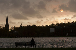 © Licensed to London News Pictures. 16/10/2017. London, UK. A person watches the sun beginning to set over the Round Pond in Kensington Gardens.  Dust brought by winds from Hurricane Ophelia has caused the sun to appear a mysterious reddish orange colour. Photo credit : Stephen Chung/LNP