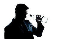 one caucasian man portrait silhouette drunk looking at an empty alcohol botlle in studio isolated white background