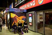 Family wait outside chain restaurants Burger King and Cafe Nero. London, UK.