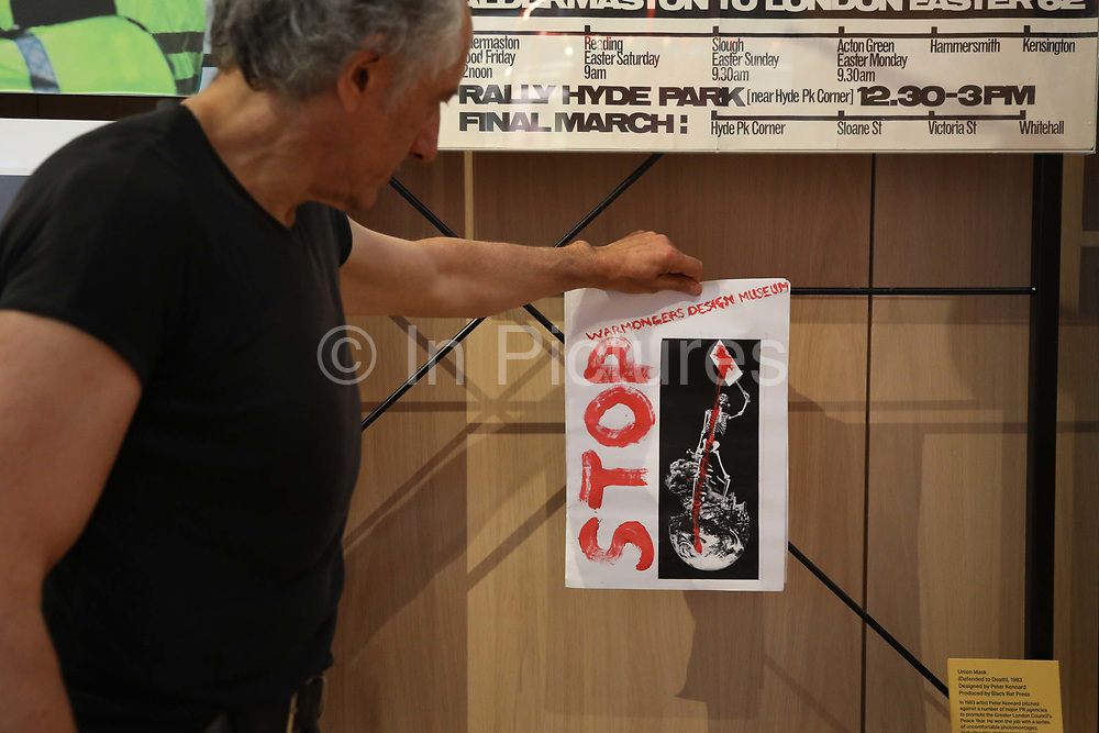 Artist Peter Kennard holds up a small poster in protest instead of his art work on show up till yesterday at the Design Museum, London, Unted Kingdom, August 02 2018. He has decided to pull his work on show in the permanent collection at the Design Museum in protest against the museums involvement with the arms industry. The Design Museum hosted an event by Leonardo, the ninth biggest arms company in the world and along with around 40 artists showing work in the exhibition Nope to Hope Kennard pulled his work in protest. A group of artist and representatives collected the work.