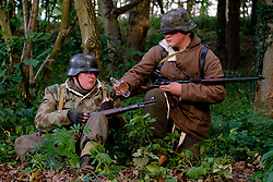 Reenactors dressed in late War German winter clothing both are wearing Parkas and Steel helmets, Short Boots and Gaiters carrying the Mauser K98 Rifle. stop for a rest in a wooded area and share a drink<br /> <br />  September 2019<br /> All Images Copyright Paul David Drabble - <br /> All rights Reserved - <br /> Moral Rights Asserted -