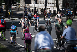 © Licensed to London News Pictures. 25/05/2020. London, UK. Cyclists queue to enter Parliament Square in Westminster on a hot summers day during Lockdown. Government has encouraged the public to use bikes to travel rather than using public transport. Photo credit: Ben Cawthra/LNP
