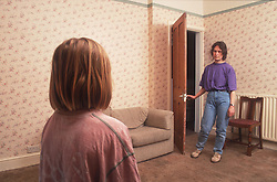 Mother standing in doorway of living room staring at young daughter who is standing opposite,