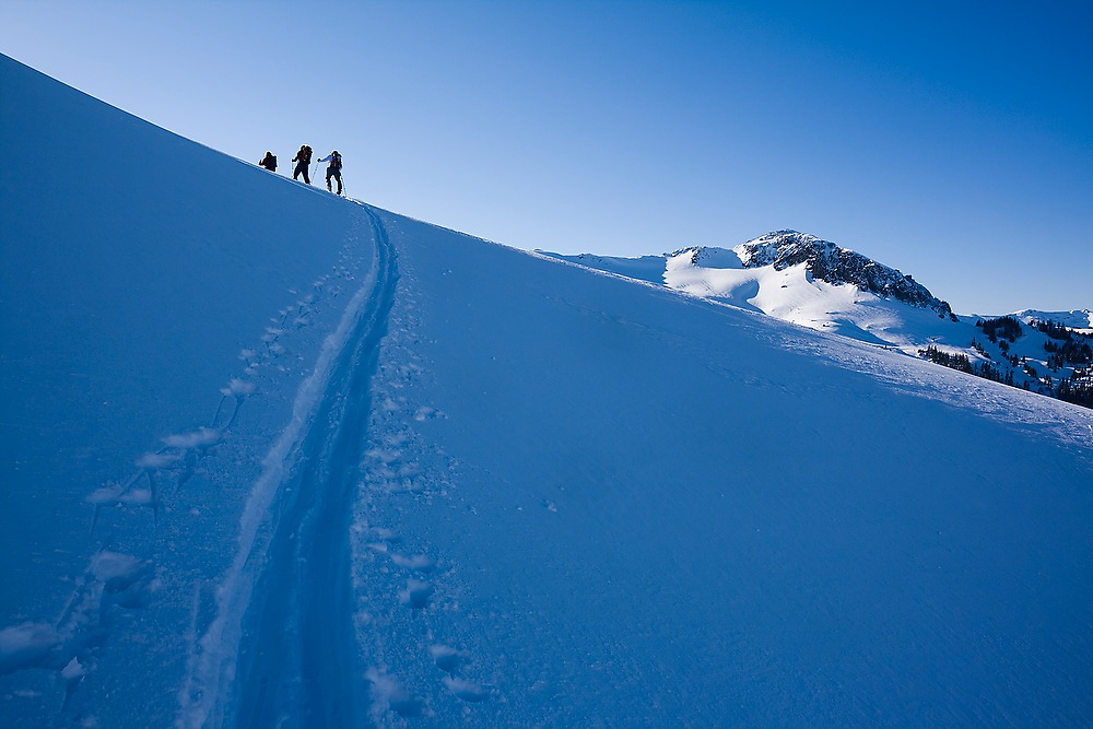 Skiers follow a ski track along Ptarmigan Ridge in the Mount Baker backcountry, Mount Baker-Snoqualmie National Forest, Washington.