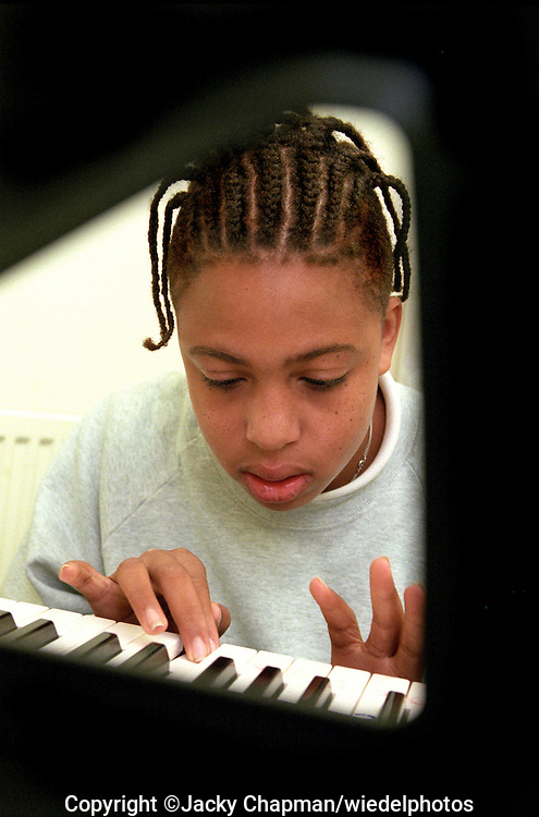 Pupils learning to play the piano at school