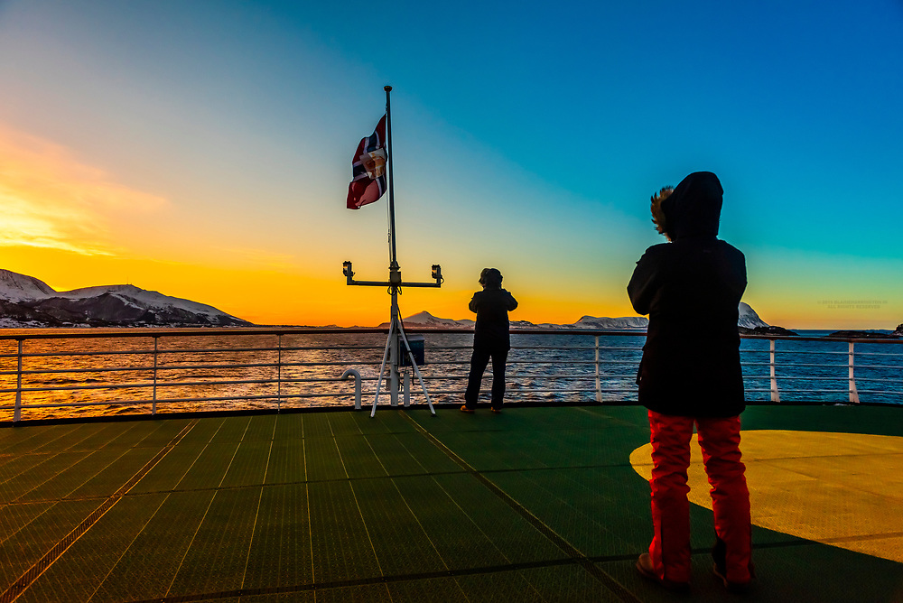 Passengers on the stern  of the Hurtigruten ship MS Vesteralen in winter enjoying the view, sailing between Alesund and Molde, Norway.