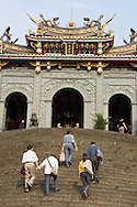 A group of people climbs the curved stone stairs to the Zhi Nan Temple in Taipei, Taiwan.