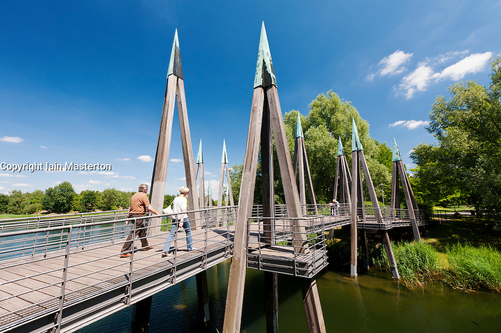 Abstract wooden footbridge crossing lake at Britzer Garden in Neukolln in Berlin Germany