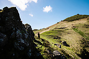 Woman out running on the cliffs and headland of the north coast of Jersey in Spring, taking in the views