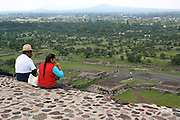 Indigenous couple sitting on top of a pyramid in Teotihuacan, Mexico. <br /> A good hour away from Mexico City is located Teotihuacan, or The City of Gods, how the Aztecs called this place. The rich legacy of Aztecs is visible in numerous pyramids and well kept murals. On the photograph an indigenous couple is sitting on the Pyramid of the Sun, the road below is called the Avenue of Death.