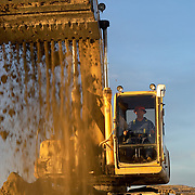 230LC Deere excavator moving a bucket of earth.