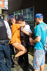 London, August 28th 2016. A woman twerks against a policeman as Europe's biggest street party, the Notting Hill Carnival gets underway.