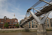 Tourists take a sightseeing tour cruise boat down the River Thames taking in some of the famous landmarks, skylines and iconic buildings in the capital, operated by City Cruises in London, England, United Kingdom. Passing Millennium Bridge.