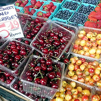 USA, Washington, Seattle. Locally grown cherries and berries at Pike Place Market.