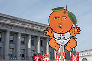 """San Francisco, USA. 19th January, 2019. The Women's March San Francisco begins with a rally at Civic Center Plaza in front of City Hall. A protester holds a sign mocking Donald Trump as an infant wearing an """"I love Putin"""" onesie. The president's head is made to look like a peach, a probable reference to impeachment. Credit: Shelly Rivoli/Alamy Live News"""