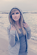 Young blond model in a hoodie outdoors at the beach