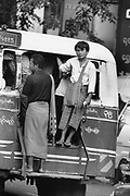 Traveller hangs out of the back of a bus as it travels through Rangoon. Burma 1999