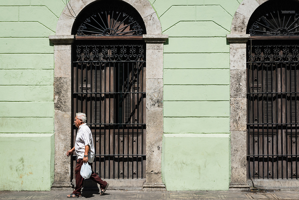 Man walking past a Colonial style building in Merida, Mexico
