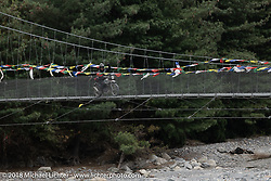 Kiwi Mike Tomas riding a suspension bridge on day-6 of our Himalayan Heroes adventure riding from Muktinath to Tatopani, Nepal. Sunday, November 11, 2018. Photography ©2018 Michael Lichter.