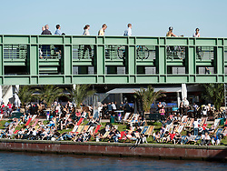 People crossing modern footbridge across Spree River with busy riverside bar to rear in Berlin Germany