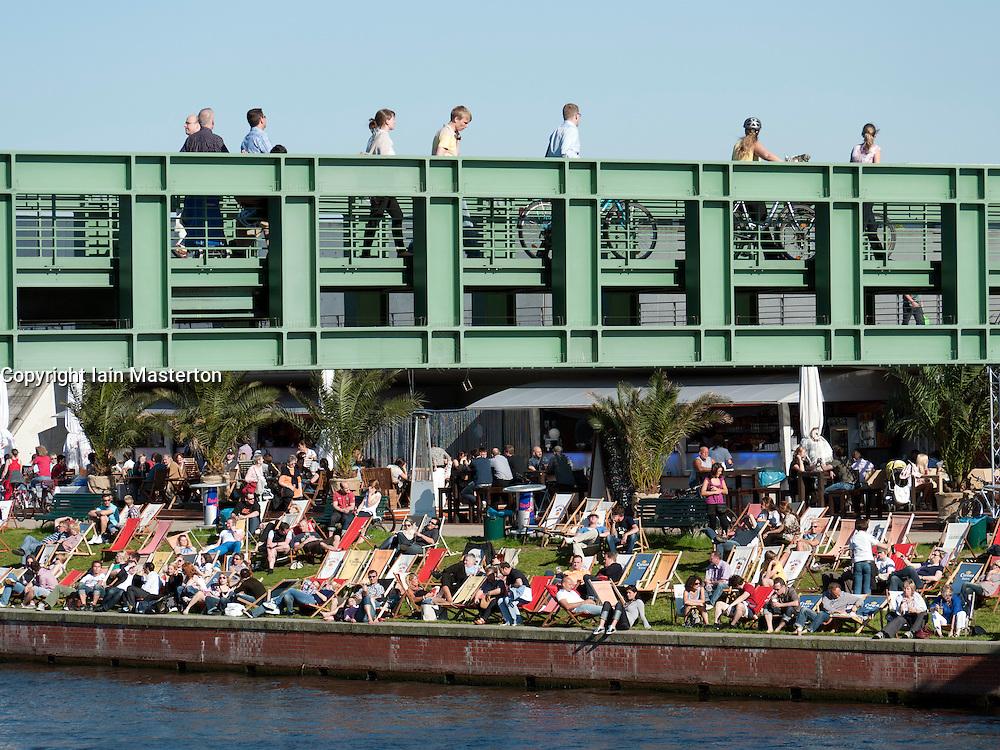 People crossing modern footbridge across Spree River with busy riverside bar to rear in Berlin Germany