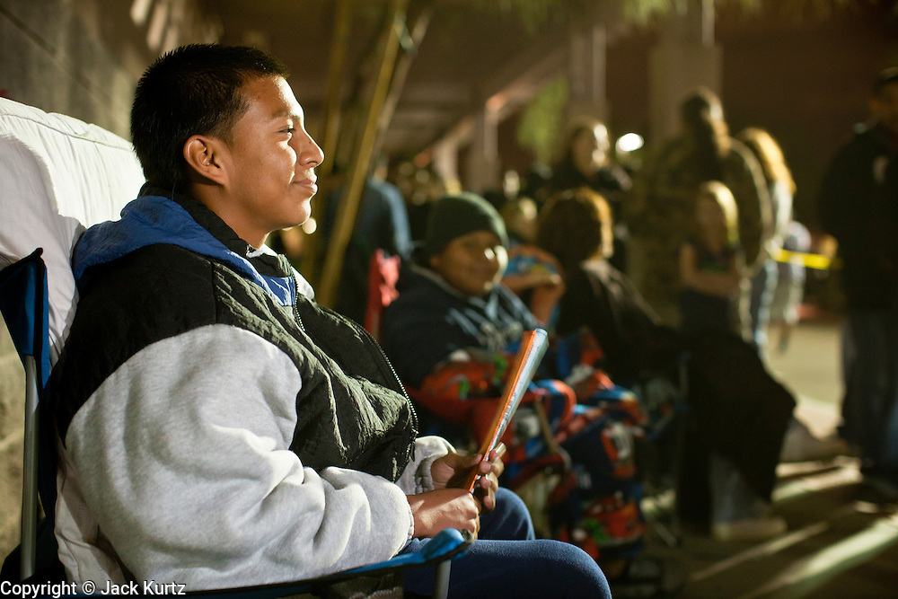 """24 NOVEMBER 2011 - PHOENIX, AZ: 22:43 Joe Martinez (CQ), 15, was first in line at the Best Buy store on Thunderbird and I 17 in Phoenix Thursday night. He said he got in line after school on Tuesday and was in line to buy the 42"""" Sharp TV. """"Black Friday,"""" the unofficial start of the holiday shopping season started even earlier than normal. Many stores, including Target and Best Buy, opened at midnight. The Best Buy at Thunderbird and I 17 showed a Harry Potter movie on the side of a rented truck in the parking lot to keep people amused while they waited for the store to open.   Photo by Jack Kurtz"""