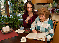"""Tamara McGonagle and Judy Buswell read through the journals of Anna Samson Bradley in preparation for their upcoming performance of """"I Have Been Busy All Day"""" depicting Bradley's life as a housewife and mother during the 1890's.   (Karen Bobotas/for the Laconia Daily Sun)"""