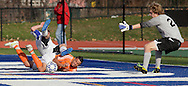 Middletown, New York  - The Webster Schroeder goalie, at right, reaches for the ball after two players collided during the New York State Class AA  boys' soccer championship game on Nov. 20, 2011.