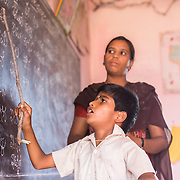 CAPTION: Until the age of five, Naveen - who has cerebral palsy - was confined to his bed. That was the point at which he got his first life-changing surgery, after which he started to receive training from Mobility India. Rehabilitation Therapy Assistant (RTA) Kavitha patiently worked with him on a one-to-one basis, teaching him how to stand, balance and walk. Since then, he has been an enthusiastic participant at his local After-School Club (ASC). In this image, we see him standing on his own two feet at the front of his class, leading his fellow attendees in a Kannada literacy session under the watchful eye of his ASC tutor. LOCATION: Mallianpura (village), Kasaba (hobli), Chamrajnagar (district), Karnataka (state), India. INDIVIDUAL(S) PHOTOGRAPHED: Naveen Kumar N. (boy) and Vathsalakumari (woman).