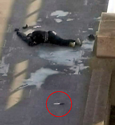 © Licensed to London News Pictures. 29/11/2019. London, UK. The body of a man lies motionless on London Bridge, close to what appears to be a knife (circled red) after police shot the man following reports of a series of stabbings. Photo credit: LNP