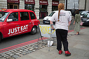 Red shoes and a red taxi. Man with orthopedic shoe waiting for a lift in London, UK.