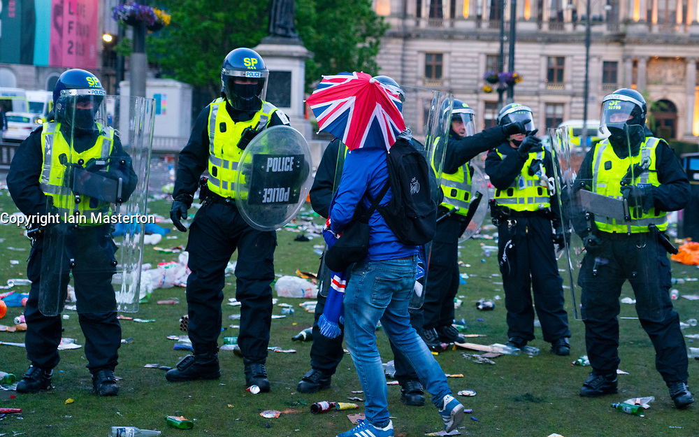 Glasgow, Scotland, UK. 15 May 202. Rangers football supporters  celebrating 55th league victory are cleared from George Square by police in riot gear on Saturday evening. In very violent scenes police were pelted with bottles and items from a nearby construction site as police pushed the supporters into the south west corner of the square. Pic; Rangers fan walks in front of police line. Iain Masterton/Alamy Live News.
