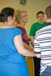 Day Service users with learning disability taking part in line dancing class with Duty Service Officer joining in the activity,